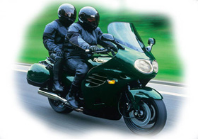 two people riding a green motorcycle