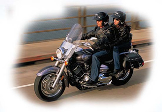 two people riding a black motorcycle